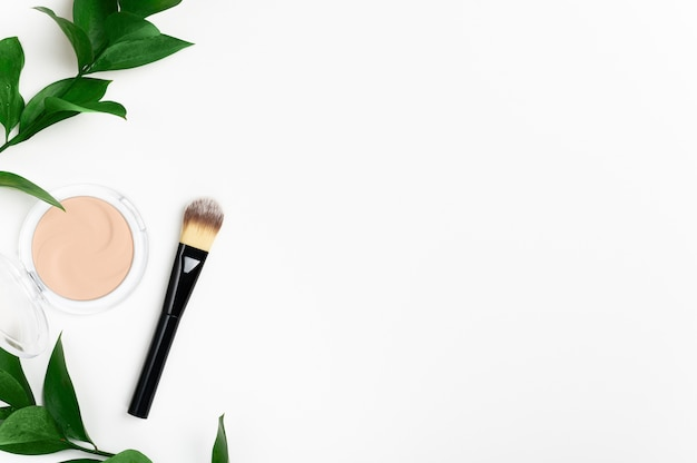 Face powder in round case and make up brush top view with green leaf