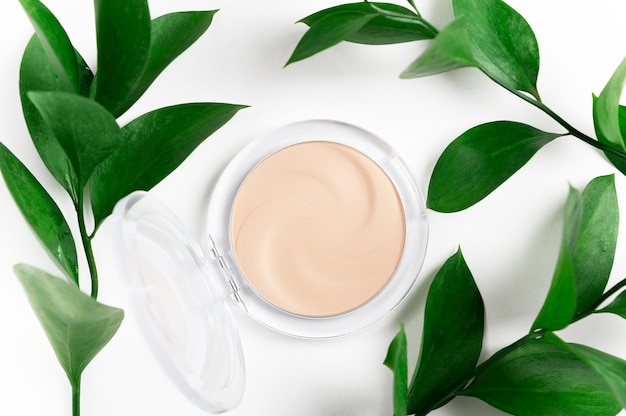Face powder in round case top view on green leaf background