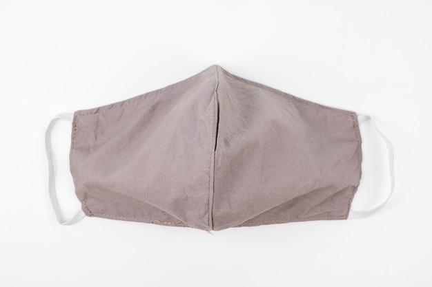 Маска защитная для лица ручной работы из тканевой ткани на белом фоне.