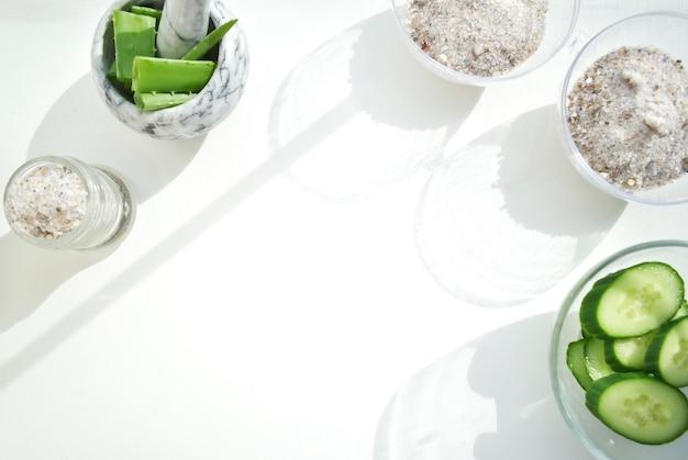Лицевые ролики, скребок для массажа гуашью, изготовлены из натурального аметиста. набор для ухода за собой. главная спа продукты на белом фоне. маски для лица с огурцом и алоэ.