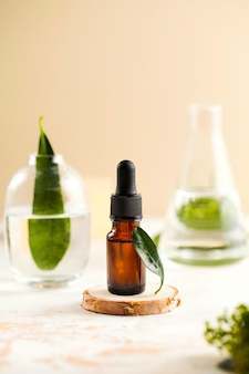 Face serum in a dark glass bottle with green leaves in transparent glass flasks in the background. skin care.