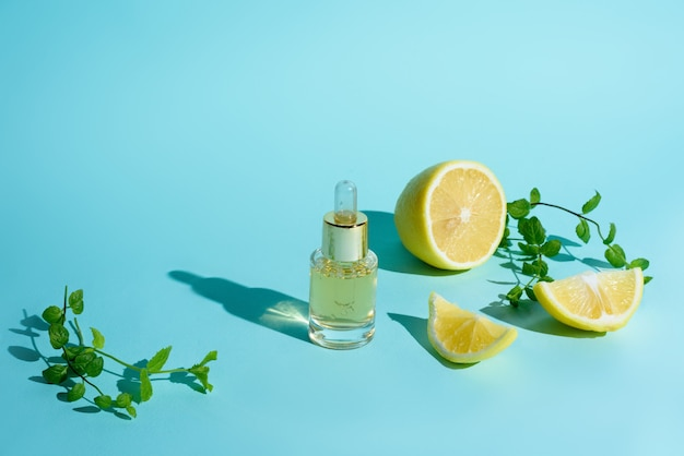 Face serum with citrus fruit lemon and vitamin c in a glass bottle with a pipette on a blue background, the concept of self-care skin care at home.