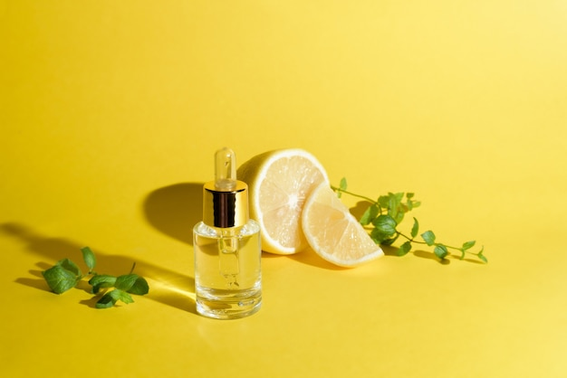 Face serum with citrus fruit lemon and vitamin c in a glass bottle with a pipette on a yellow background