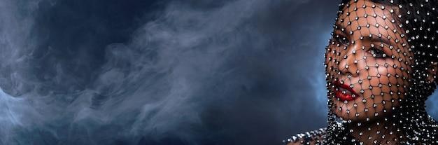 Выстрел в лицо портрет азиатской красавицы. девушка украшает голову бриллиантом crystal net над темным дымом фон, пространство для копирования баннера, взгляд крупным планом мода
