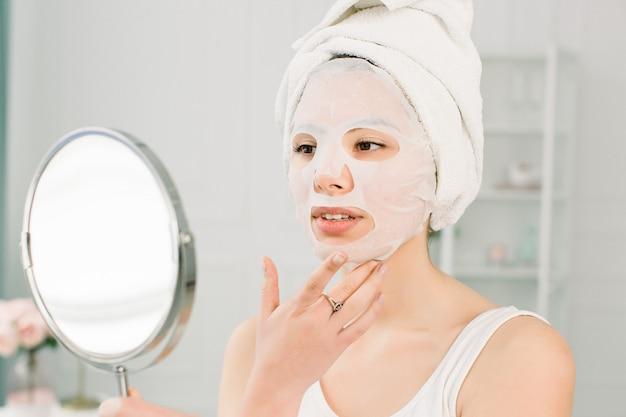 顔のスキンケアと美容トリートメント。鏡を見て、顔にシート保湿マスク、頭に白いタオルを持つ女性。