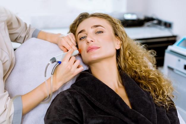 Уход за кожей лица. конец-вверх довольно белокурой курчавой женщины получая лицевую гидро пилинг обработки microdermabrasion на косметологии spa clinic.