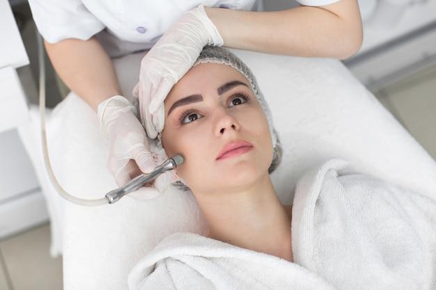 フェイススキンケア。コスメティックビューティースパクリニックでフェイシャルハイドロマイクロダーマブレーションピーリングトリートメントを受けている女性のクローズアップ。ヒドラ掃除機。角質除去、若返り、水分補給。美容。