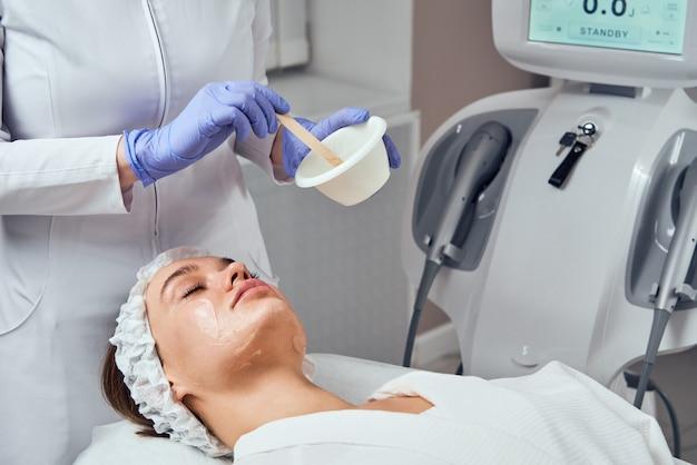 フェイススキンケア。美容スパクリニックで顔のハイドロマイクロダーマブレーションの剥離治療を受ける女性のクローズアップ。 hydra掃除機。角質除去、若返り、水分補給。美容学。