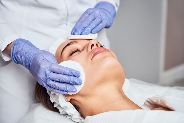 Face skin care. close-up of woman getting facial hydro microdermabrasion peeling treatment at cosmetic beauty spa clinic. hydra vacuum cleaner. exfoliation, rejuvenation and hydration. cosmetology.