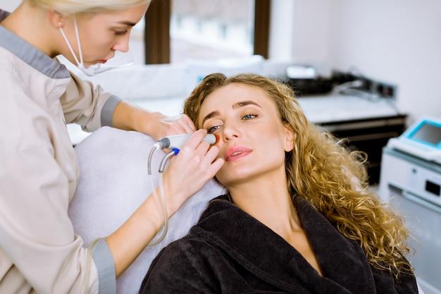 Уход за кожей лица. профессиональная женщина-косметолог, выполняющая гидрафациальную процедуру в косметологической клинике. пылесос hydra.