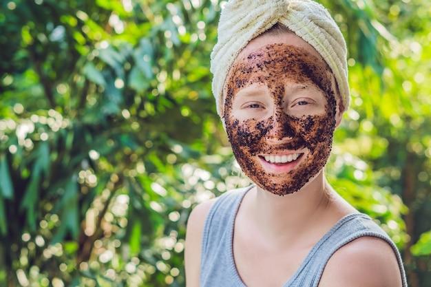 フェイススキンスクラブ。自然なコーヒーマスクを適用するセクシーな笑顔の女性モデルの肖像画。美容製品で覆われた顔を持つ美しい幸せな女性のクローズアップ。高解像度