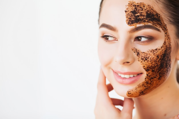 Face skincare young charming girl makes a black charcoal mask on her face