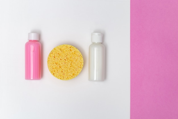 Face sponge yellow colored, moisturizer, cleanser in small bottles on paper