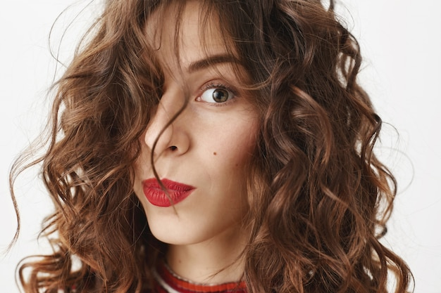 Face of stylish beautiful woman with red lipstick and curly haircut