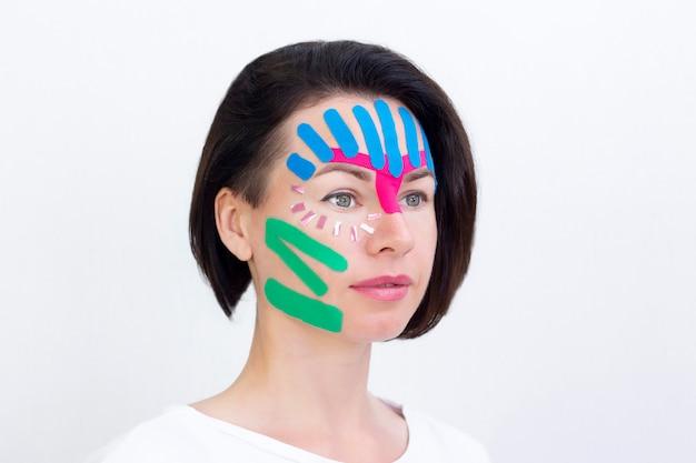 フェイステーピング、美容のしわテープを使用した女の子の顔のクローズアップ。顔の美的テーピング。しわを減らすための非侵襲的なアンチエイジングリフティング法