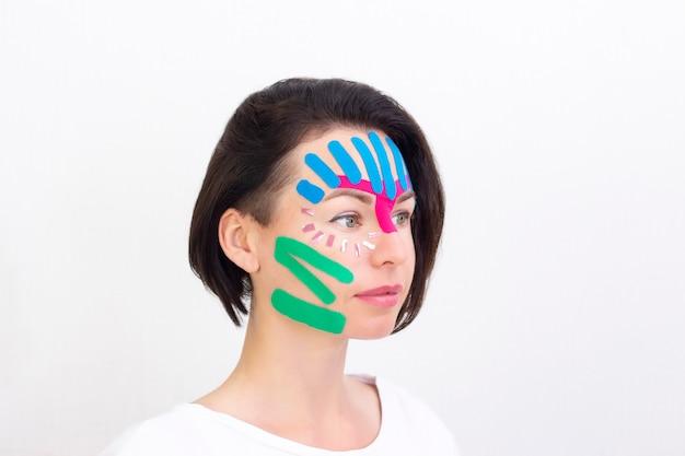 顔のテーピング、美容用のしわ防止テープによる女の子の顔のクローズアップ。美的なテーピングに直面します。しわを減らすための非侵襲的なアンチエイジングリフティング法