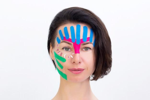フェイステーピング、化粧品のしわ防止テープによる女の子の顔のクローズアップ。顔の美的テーピング。