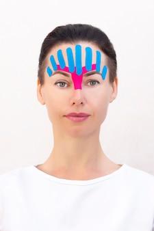 顔のテーピング、美容用のしわ防止テープによる女の子の顔のクローズアップ
