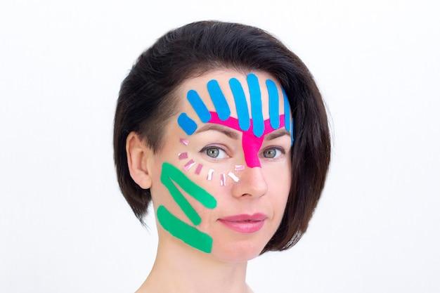 顔のテーピング、美容用のしわ防止テープによる女の子の顔のクローズアップ。