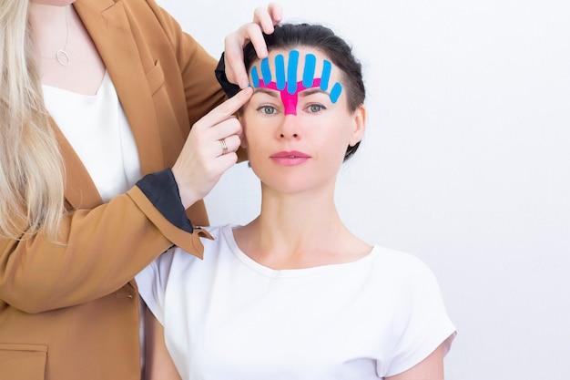 顔のテーピング、化粧品のしわ防止テープで若い女性の顔のクローズアップ