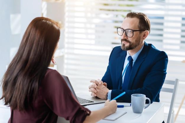面と向かって。会社の将来を計画している間、テーブルに座っているプロの熟練した2人の同僚