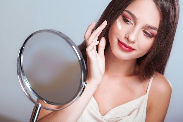 Face treatment. woman with healthy face applying cosmetic cream under the eyes