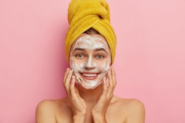 세안 및 위생 개념. 쾌활한 젊은 유럽 여성은 비누로 얼굴을 청소하고 양손으로 뺨을 만지며 머리에 포장 된 노란색 수건을 착용하고 긍정적으로 보이고 먼지를 제거합니다.