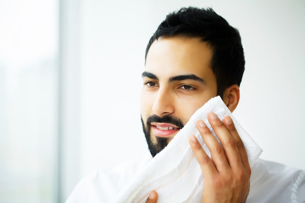 Face washing. happy man drying skin with towel