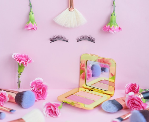 Face with false eyelashes and flowers, premium makeup brushes on a colored pink background, creative cosmetics flat lay