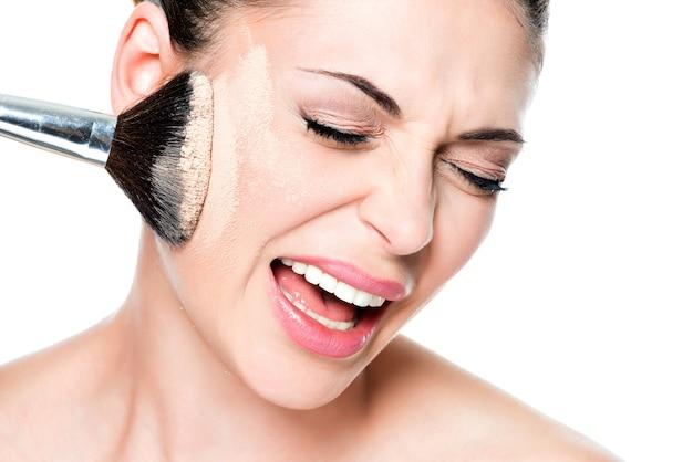 Volto di una donna con polvere sulla pelle della guancia isolato su bianco