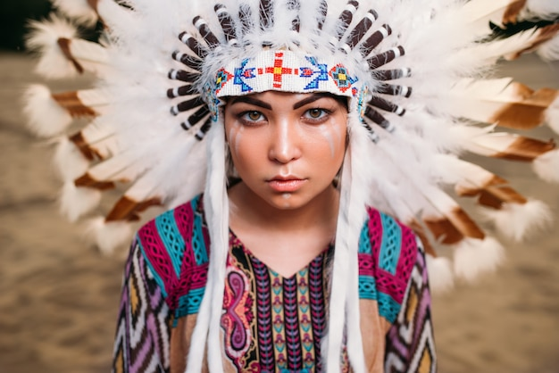 Face of young american indian woman, cherokee, navajo. headdress made of feathers of wild birds
