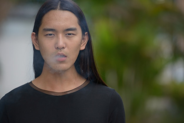 Face of young asian man with long hair smoking at the park
