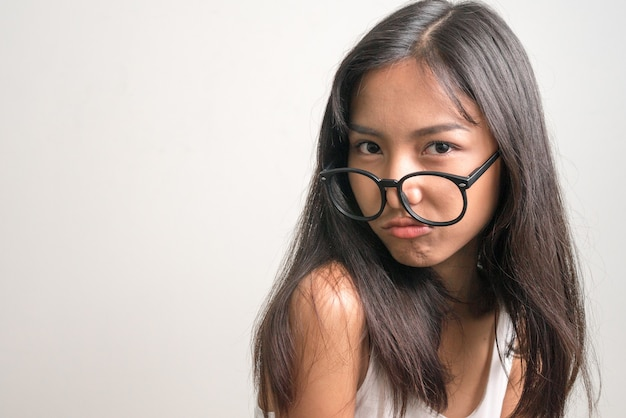 Face of young beautiful asian teenage girl with eyeglasses