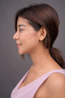 Face of young beautiful asian woman against gray wall