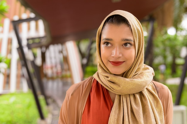 Face of young beautiful indian muslim woman thinking in the city with nature