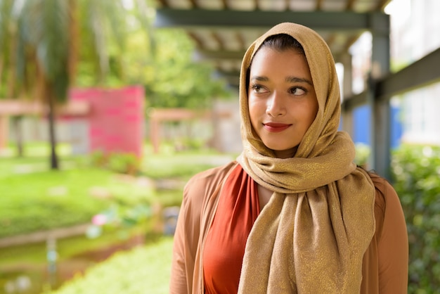 Face of young beautiful indian muslim woman thinking at the park