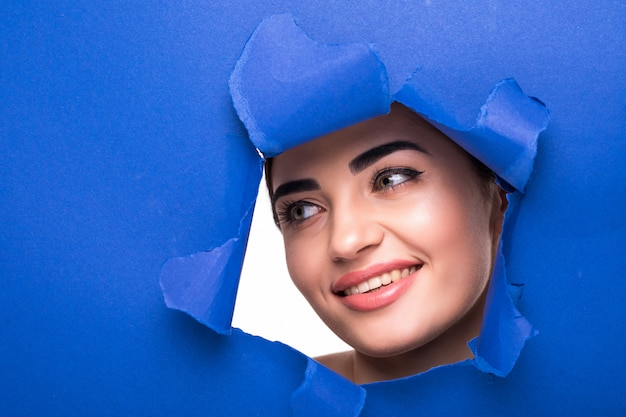 The face of a young beautiful woman with a bright make-up and puffy blue lips peers into a hole in blue paper.