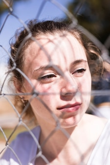 Face of young girl at grid