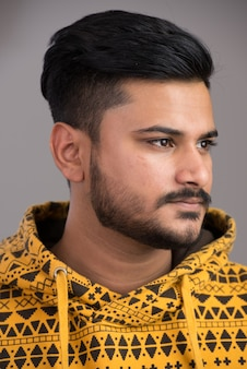 Face of young handsome indian man thinking