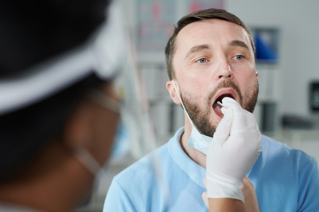 Face of young male patient being tested for covid with oral swab held by gloved female nurse or clinician while sitting in front of her
