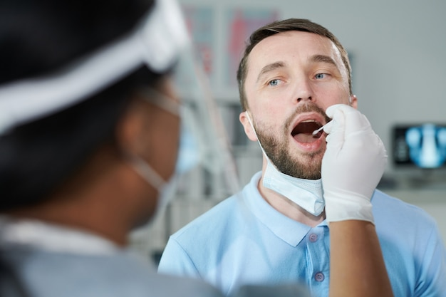 Face of young male patient with open mouth looking at female clinician in protective workwear while being tested for covid with oral swab in clinics