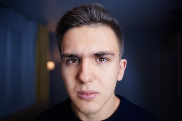 Face of young white man with brown eyes, short hair, and sullen look, against the wall of dark blue room.