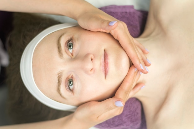 Face of young woman during procedure of applying cream. healthy facial massage, lymphatic drainage massage. top view