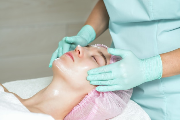 Face of young woman is receiving a cream in beauty salon.