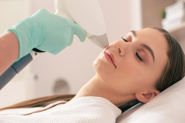 Face of young woman lying with closed eyes and undergoing laser hair removal procedure