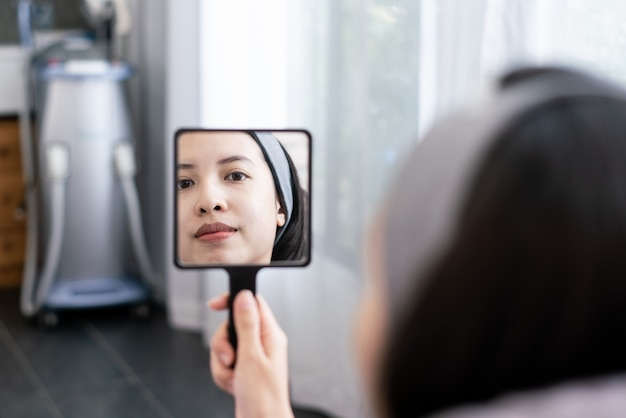 Face of young woman and reflection in the mirror. after or before plastic aesthetic facial surgery in beauty clinic.