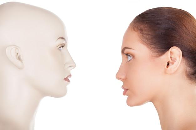 Взгляните на свою проблему. вид сбоку красивой молодой женщины, стоящей перед манекеном и смотрящей на него, стоя изолированной на белом фоне