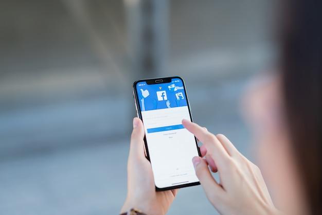 Рука нажимает на экран facebook
