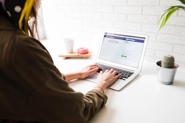Женщина заходит на сайт facebook на ноутбуке