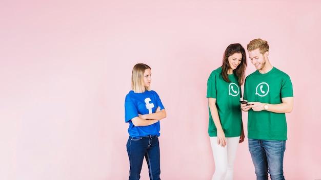 Женщина в футболке facebook, глядя на счастливую пару, используя сотовый телефон